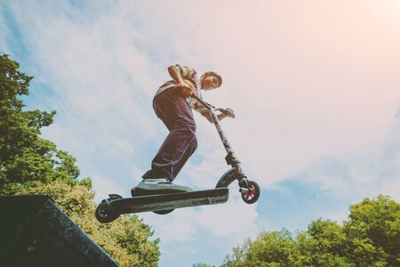 Boy riding a kick scooter in a park. Beautiful background Imagens