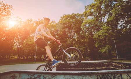 Boy jumping with his bmx in the park. Beautiful background