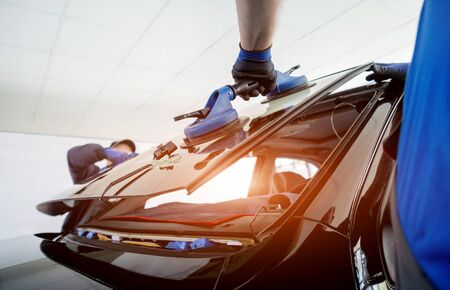 Travailleurs spéciaux de l'automobile remplaçant le pare-brise ou le pare-brise d'une voiture dans le garage de la station-service automobile. Fond