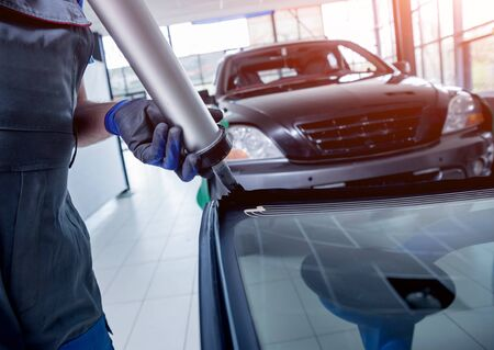Automobile special workers replacing windscreen or windshield of a car in auto service station garage. Background Stock fotó