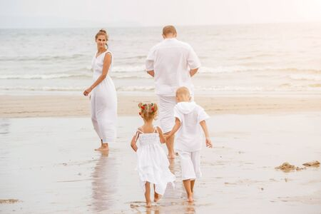 Happy young family on the sunset at the beach. Stock fotó