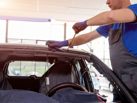 Automobile special workers remove old windscreen or windshield of a car in auto service station garage. Background Stock Photo