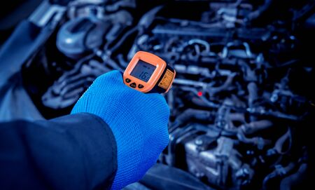 infrared laser thermometer in hand. Motor temperature measurement in the car service Фото со стока