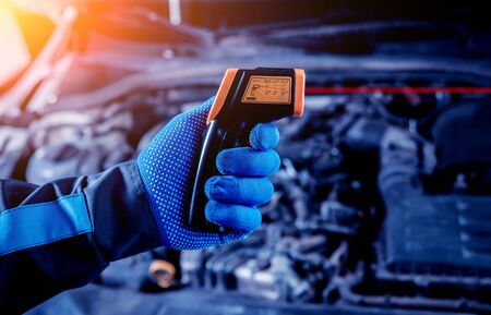 infrared laser thermometer in hand. Motor temperature measurement Фото со стока