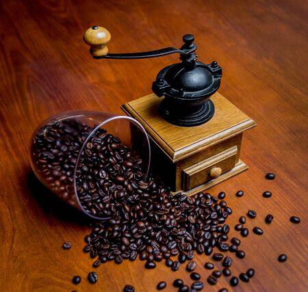 Elegant coffee grinder with scattering of coffee beans on the table Standard-Bild