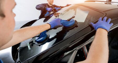 Automobile special workers replacing windscreen of a car in auto service Standard-Bild