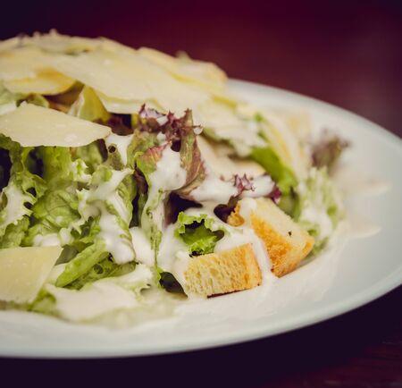 Fresh salad with fish on a white plate. Restaurant Standard-Bild