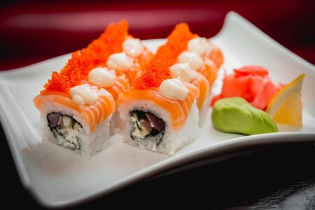 Sushi on a white plate. Rolls. The restaurant background.