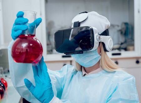 Doctor in virtual reality glasses examines the drug in laboratory.