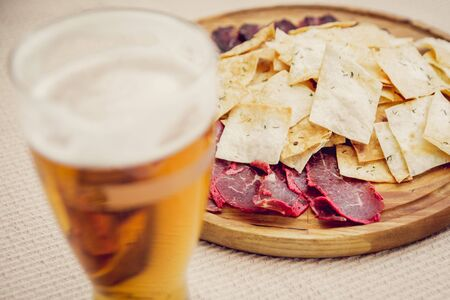 Meat and chips on a wooden plate with beer.