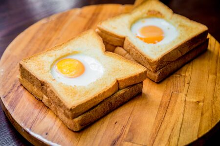 Toast bread with egg inside on the board Standard-Bild