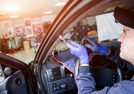 Automobile special workers remove old windscreen of a car in auto service