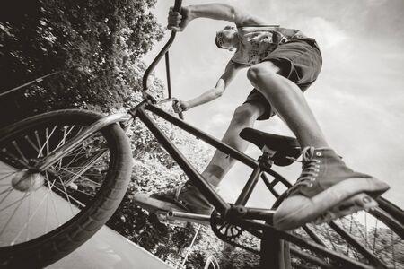 Boy riding a bmx in a park.