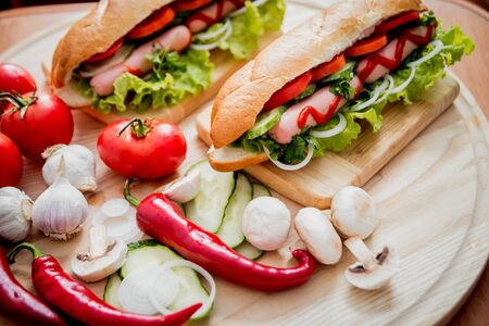 Large hot dog with vegetables on the table.