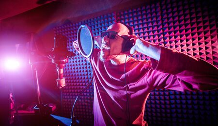 The singer sings with a microphone in the recording studio. Standard-Bild