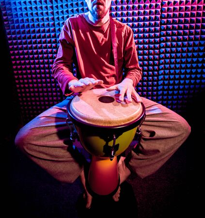 Young man playing on djembe in sound recording studio. Standard-Bild