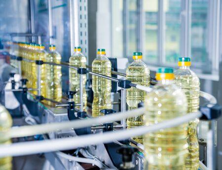 Bottling line of sunflower oil in bottles. Vegetable oil production plant