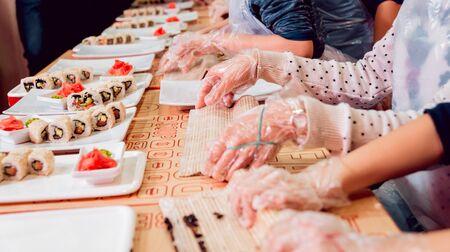 Children prepare sushi and rolls. Master-class restaurant.