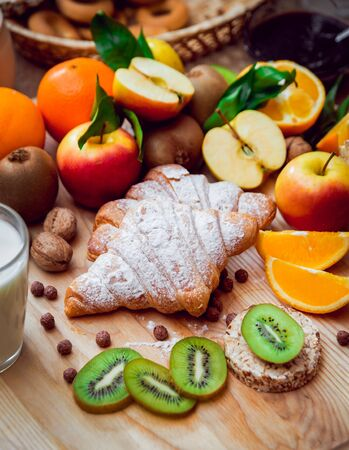 Beautiful breakfast. Milk fruits, bread and croissant. Background.
