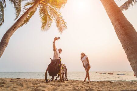 Disabled man in a wheelchair with his wife on the beach. Archivio Fotografico