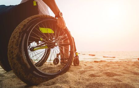 Disabled man in a wheelchair on the beach.