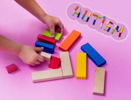A child with an autism spectrum disorder builds a house from a wooden constructor. Concept of autism. 免版税图像