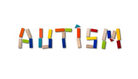 Concept of autism. Wooden word on colored background