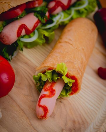 Large hot dog with vegetables on the table. Kitchen Foto de archivo