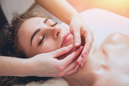 Belle femme dans un salon spa se massage du visage Banque d'images