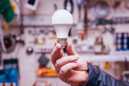 Man's hands holding shiny lamp. Light background