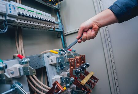 Electricians hands testing switches in electric box. Electrical panel with fuses and contactors. Background and texture