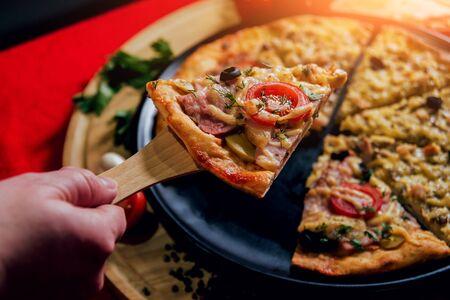 A slice of pizza in his hand. A restaurant. Foto de archivo