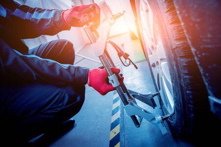Car mechanic installing sensor during suspension adjustment. Wheel alignment work at repair service station Stock fotó
