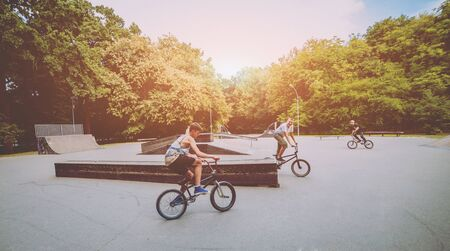 Company of young people on BMX. Beautiful background.