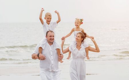 Happy young family on the sunset at the beach.