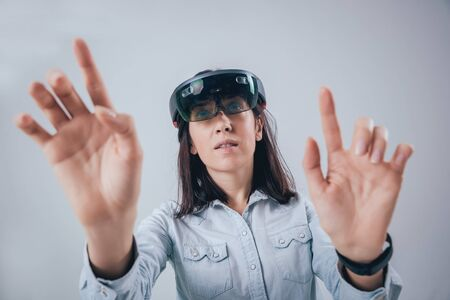 Woman wearing augmented reality goggles. White background in studio.