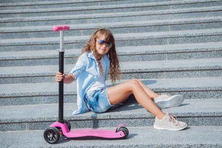 Little girl posing with scooter outdoors. Street city background.