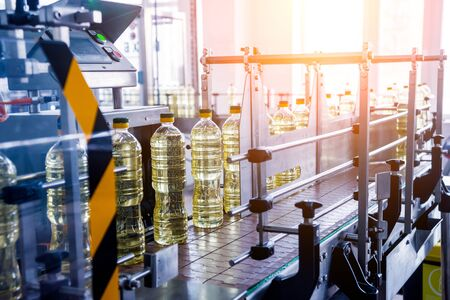 Bottling line of sunflower oil in bottles. Vegetable oil production plant.