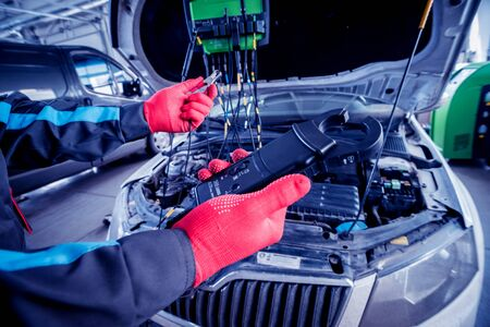 Auto mechanic uses a voltmeter to check the voltage level.