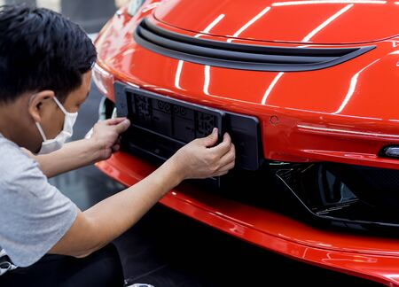 Technician changing car plate number in service center.