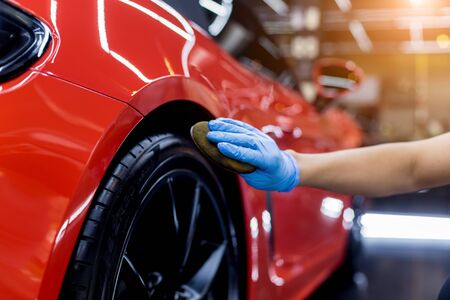 Car service worker polishing car wheels with microfiber cloth. Standard-Bild