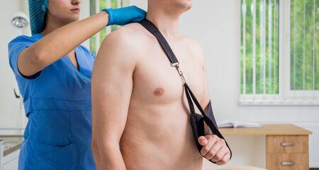 Nurse putting a sling on patients arm that is broken. Injury. Broken arm, shoulder.