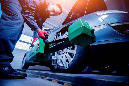 Car mechanic installing sensor during suspension adjustment. Stock fotó