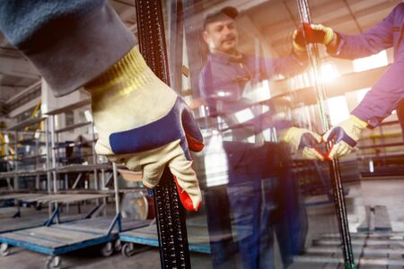 Workers transfer the glass. At the factory for the production of windows
