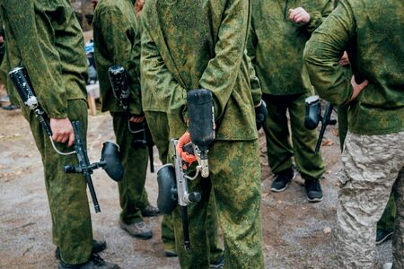 Men with guns playing at paintball. Outdoors