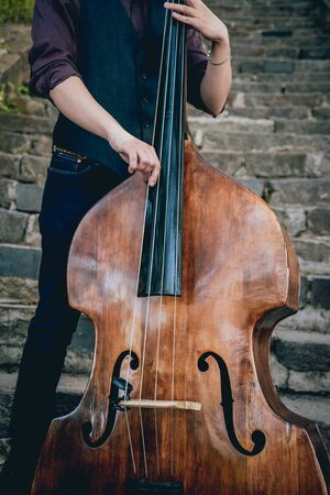 View of musician playing contrabass at the street. Musical Instrument