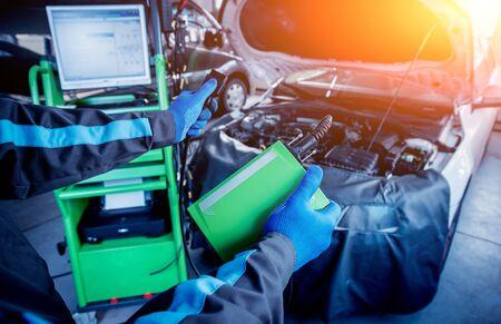 Professional car mechanic working in auto repair service. Engine computer diagnostics