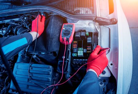 Auto mechanic uses a voltmeter to check the voltage level. Car repair. Service station. Archivio Fotografico