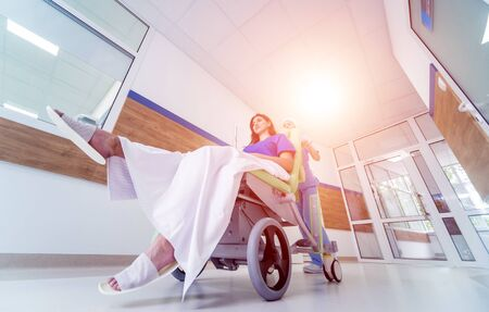 Nurse moves mobile medical chair with patient at hospital. Medical equipment. Concept Stockfoto