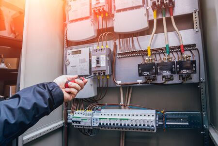 Electricians hands testing switches in electric box. Electrical panel with fuses Imagens